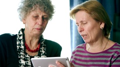 Elderly women sit at home and discuss in a social network to your tablet with Stock Footage