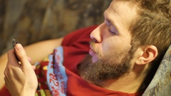 One white young brunette curly-bearded man uses the phone close-up hands using Stock Footage