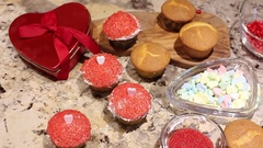 Hand grabs valentines candy hearts from baking scene on counter top Stock Footage
