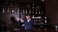 Bartender with shaker making cocktail in modern bar. Handsome barman shake drink Stock Footage