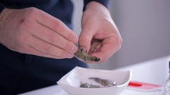 Close up shot of male hand cleans raw shrimps in the kitchen Stock Footage