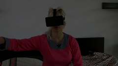 Girl relaxing home while playing game using VR equipment Stock Footage