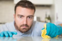 Man cleaning home with protective gloves Stock Photos