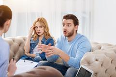 Emotional young man telling the psychologist about his family problems Stock Photos