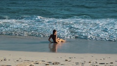 Young brunette girl lying down on wet sand on ocean coast line on windy day Stock Footage