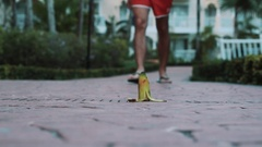 Man legs in flip flops walk toward banana peel, slipped on it and falls down Stock Footage
