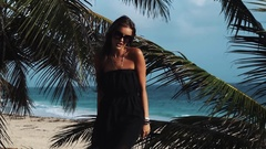 Young woman in black dress and sunglasses dancing under palm tree at ocean shore Stock Footage
