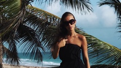 Young woman in black dress, sunglasses dance sing under palm tree at sea shore Stock Footage