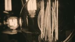 Incandescent tungsten filament trembling in light bulb, creative interior design Stock Footage
