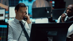 4K Financial trader in busy stock exchange negotiating a deal over the phone Stock Footage