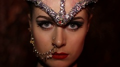 Pretty woman in sparkling feather headdress slowly opens eyes and looks at the Stock Footage