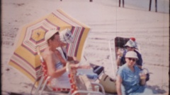Senior adults relax in the sun at the beach, 4034 vintage film home movie Stock Footage