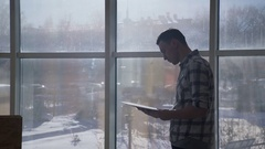 Man at the window looking documents that iterates over in his hands Stock Footage