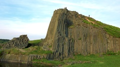 A columnar basalt rock by a lake, the blue bright sky in the background Stock Footage