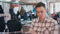 Young man sitting in a public place and making pencil writing on paper Stock Footage