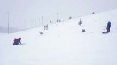 Kids and adults enjoying a small ski hill in suburban Canada.  Stadium lights Arkistovideo