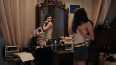 Worried woman in denim shorts and white top looking into mirror, try on clothes Stock Footage