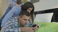 Young woman and her daughter are fooling on the man's back on the bed Stock Footage