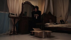 Woman in black crying in bedroom over cardboard box with picture frame in hands Stock Footage
