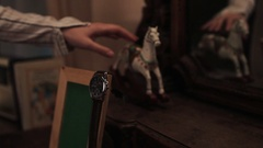 Female hand push rocking horse toy swing on table, picture frame green key watch Stock Footage