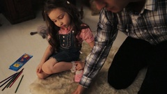 Man in plaid shirt observe his little daughter pictures on bedroom floor Stock Footage