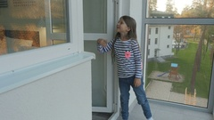 Little girl invite her parents on a balcony in the apartment Stock Footage