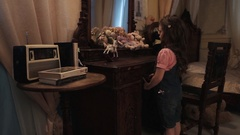 Little girl take plush bunny toys of wooden table with mirror in bedroom Stock Footage