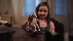 Little girl play with miniature white rocking horse on wooden table in bedroom Stock Footage