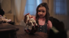 Little scared girl pull miniature white rocking horse on wooden table in bedroom Stock Footage
