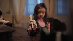 Little afraid girl push miniature white rocking horse on wooden table in bedroom Stock Footage