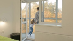Little girl is fooling with her father on the balcony and in the room on the bed Stock Footage