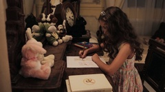 Little girl in floral dress coloring bunny picture with pencil on dressing table Stock Footage