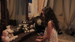 Little girl in floral dress take plush bunny toys of dressing table in bedroom Stock Footage