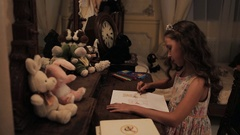 Little girl in flower dress coloring bunny picture with pencil on dressing table Stock Footage