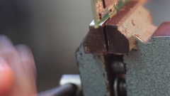 Put electronic circuit in the vise for dismantling Stock Footage