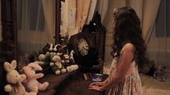 Little girl in floral dress take plush rabbit toys of dressing table in bedroom Stock Footage