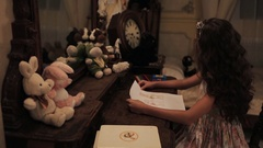 Little girl in floral dress put bunny picture on wall over dressing table Stock Footage
