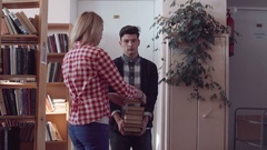 Young people gathering pile of books Stock Footage