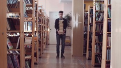 Bewildered student with pile of books Stock Footage