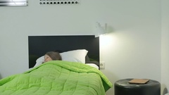 Little girl wake up from dream, streches herself and use the tablet on a bed Stock Footage