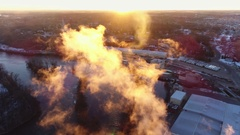 Aerial flyby of beautiful factory emissions illuminated in the sunrise Stock Footage