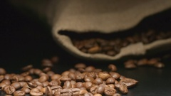 SLOW MOTION: Coffee beans fall near a lying cloth bag Stock Footage