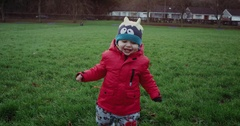 Happy little boy in red jacket running with smile in park. Child running on Stock Footage