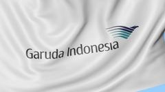 Waving flag of Garuda Indonesia against blue sky background, seamless loop Stock Footage