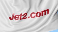 Waving flag of Jet2 com against blue sky background, seamless loop. Editorial 4K Stock Footage