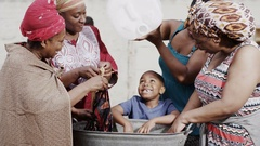 4K African family of different generations work together to wash clothes by hand Stock Footage