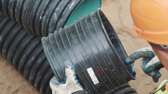 Builder in hard had applying blue gel with finger on edge of black plastic pipe Stock Footage