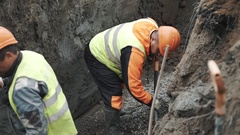 Workers in orange hard hats rowing macadam with shovels in trench, slowmotion Stock Footage