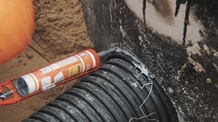 Builder applying sealant on seam between ribbed plastic tube and concrete hole Stock Footage