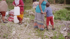 4K Poor African family filling water containers to take back to village Stock Footage